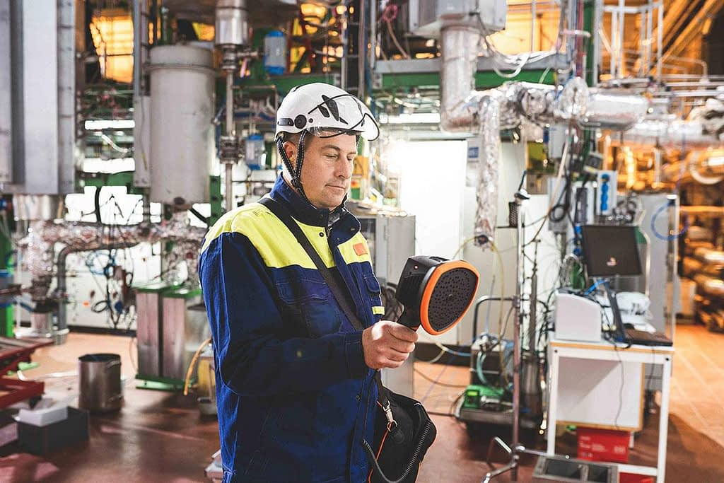 Maintenance man holding and looking down at an ultrasonic leak detector